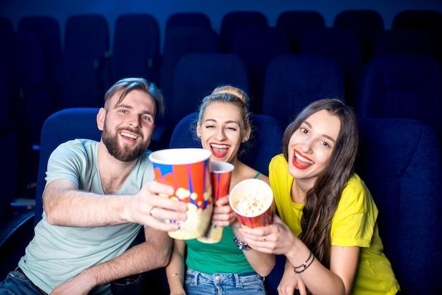 Amici felici che si divertono seduti insieme al popcorn al cinema