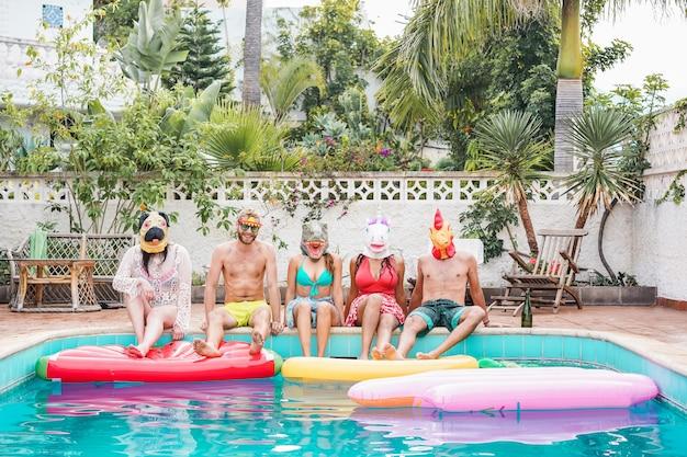 Amici felici che si divertono con air lilo ball e maschere da festa seduti accanto alla piscina - i giovani alla moda godono della villa estiva