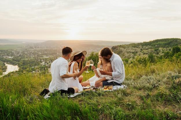 Amici felici sulla collina che hanno picnic in una soleggiata giornata estiva.