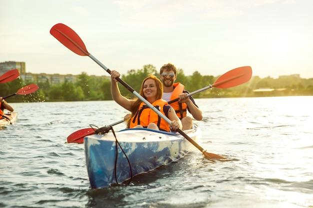 Amici felici in kayak sul fiume con il tramonto sullo sfondo