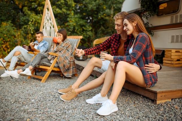 Amici felici fa selfie sul picnic al campeggio nella foresta