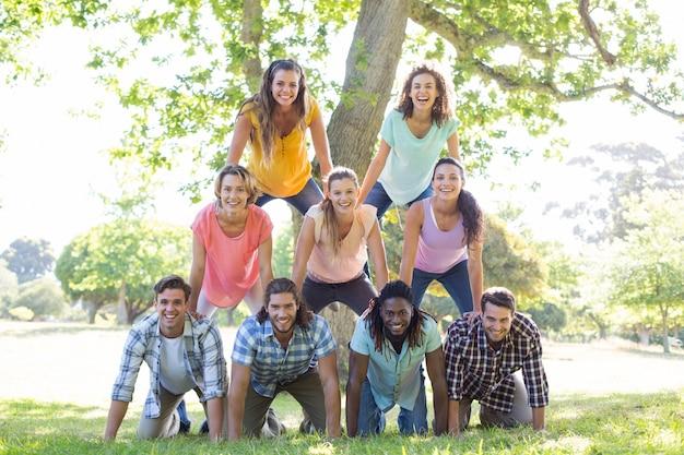 Amici felici nel parco che fa piramide umana