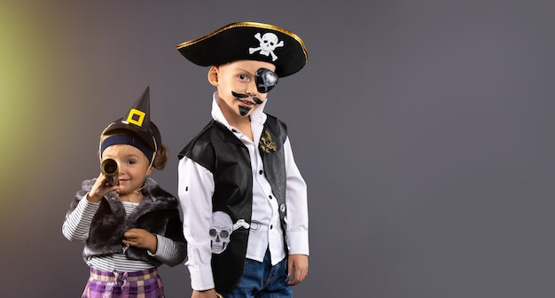 Amici felici, ragazzo pirata e piccola strega per halloween. bambini allegri pronti a festeggiare.