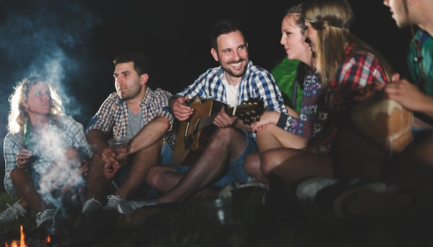 Amici felici che suonano musica e si godono il falò nella natura