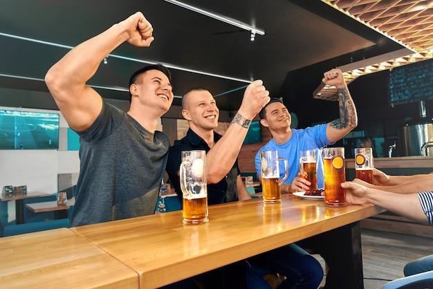 Amici felici seduti al pub e guardare insieme la partita di calcio. amici maschi che incoraggiano ridendo e bevendo gustosa birra nella caffetteria nei fine settimana. concetto di felicità e fan.