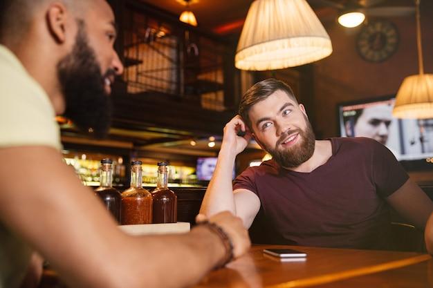 Amici felici seduti al tavolo e parlando al bar