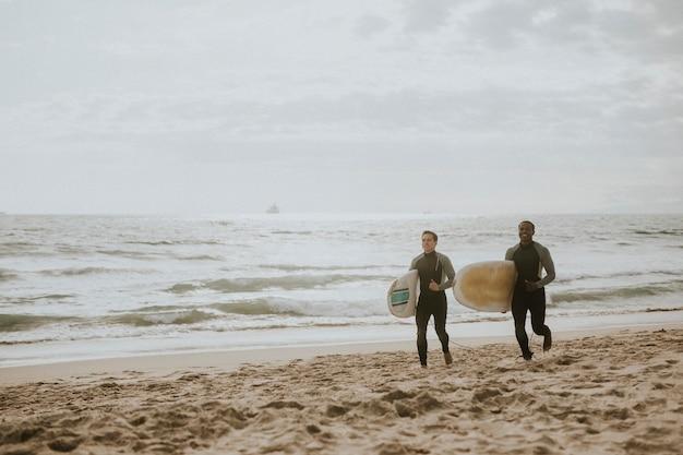 Amici felici che fanno surf in spiaggia