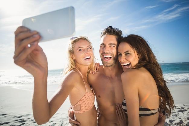 Amici felici che prendono selfie sulla spiaggia