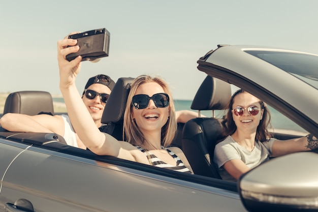 Amici felici che prendono selfie in auto