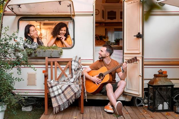 Amici felici in un furgone che suonano e cantano