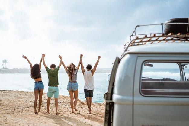 Amici felici che camminano sulla spiaggia e si alzano le mani