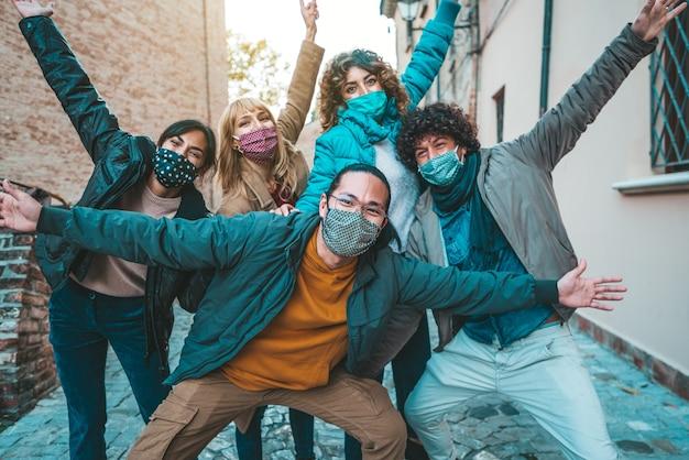 Amici felici che camminano sulla strada della città - nuovo concetto normale con i giovani che si divertono insieme coperti da maschere facciali