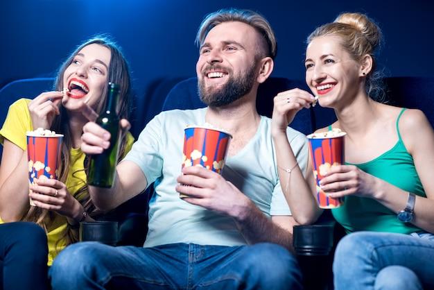Amici felici che guardano film seduti insieme a popcorn al cinema