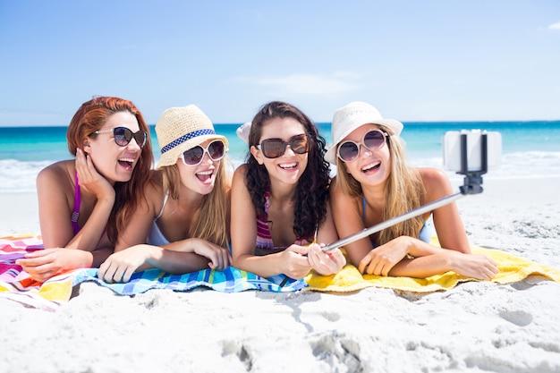 Amici felici che indossano occhiali da sole e prendendo selfie