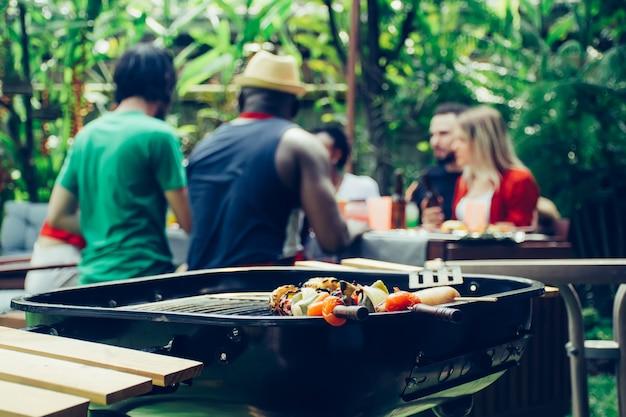 Amici felici con barbecue party in natura