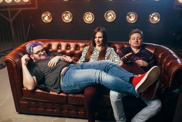 Felice amicizia, trio ah ah sul divano, festa in studio musicale. gli amici si siedono sul divano e ridono