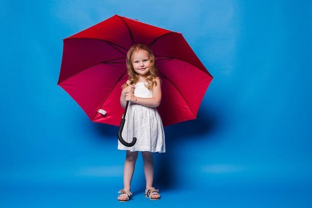 Bambino divertente felice con l'ombrello rosso che posa sulla parete blu.