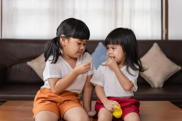 Felice e divertente ragazza due sorelle che si abbracciano e ridono con amore