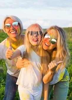Ragazze felici e divertenti ricoperte di vernice nel campo verde