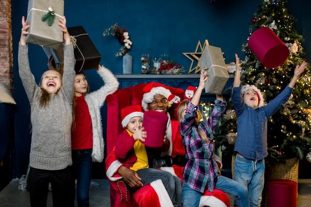 Bambini divertenti felici che sostengono i regali di natale