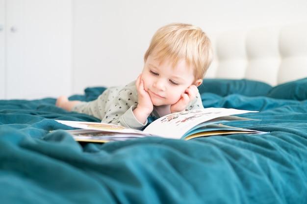 Ragazzino divertente felice in pigiama leggendo il libro sdraiato nel letto dei genitori