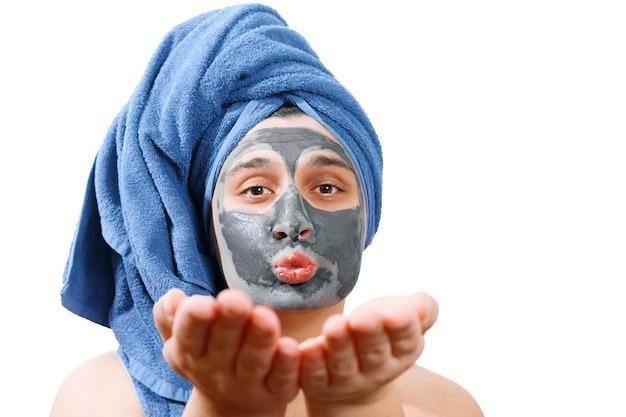 Felice uomo divertente con maschera per la pelle, l'uomo manda un bacio d'aria, l'uomo ama fare una maschera per la pelle