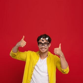 Felice uomo divertente in camicia gialla con molti occhiali sul viso, mostrando il pollice in alto isolato su sfondo rosso
