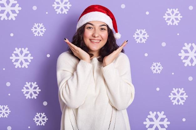 Felice divertente giovane femmina sorridente sinceramente, guardando direttamente la fotocamera, indossa maglione bianco e cappello rosso di babbo natale