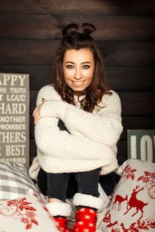 Felice ragazza giovane divertente in un maglione vintage lavorato a maglia e calzini rossi sul letto