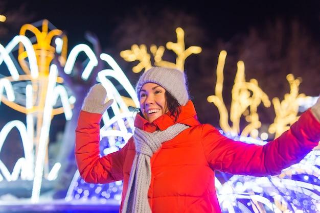 Felice divertente giovane donna con vestiti invernali sfondo sera luci della città illuminazione natale
