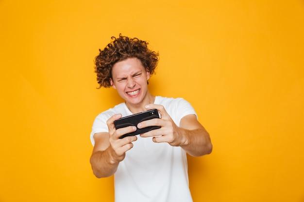 Uomo felice del giocatore in maglietta casuale che gioca i video giochi online sullo smartphone