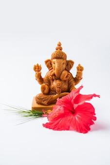 Happy ganesh chaturthi greeting card che mostra la fotografia di lord ganesha idol con pooja o puja thali, bundi laddu/modak, durva e hibiscus o jasvand flower