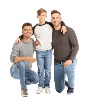Felice coppia gay con bambino adottato su superficie bianca