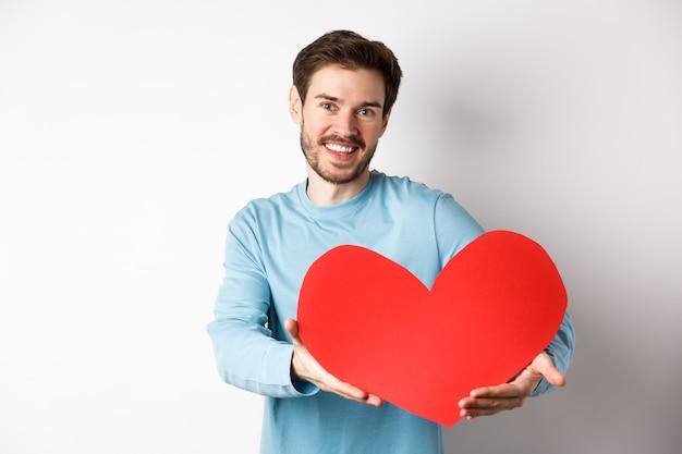 Felice uomo gay che dà un grande cuore rosso al suo amante il giorno di san valentino, concetto di appuntamento romantico e celebrazione dell'amore, in piedi su sfondo bianco