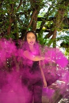 Ragazza felice, bella ragazza felice con bastone di fumo colorato con luce naturale, fuoco selettivo.