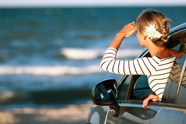 Una ragazza felice in macchina in riva al mare nella natura in viaggio di vacanza
