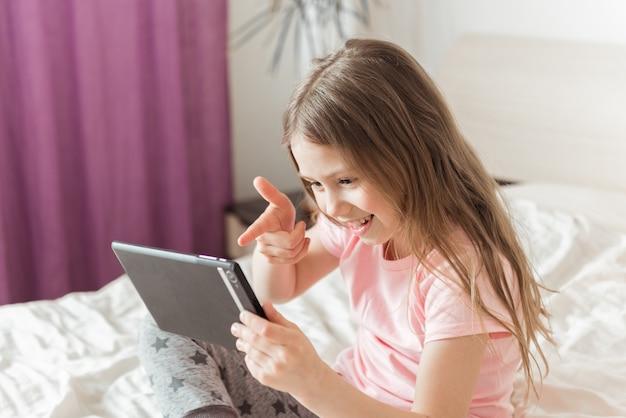 Ragazza felice in chat online a casa sul letto