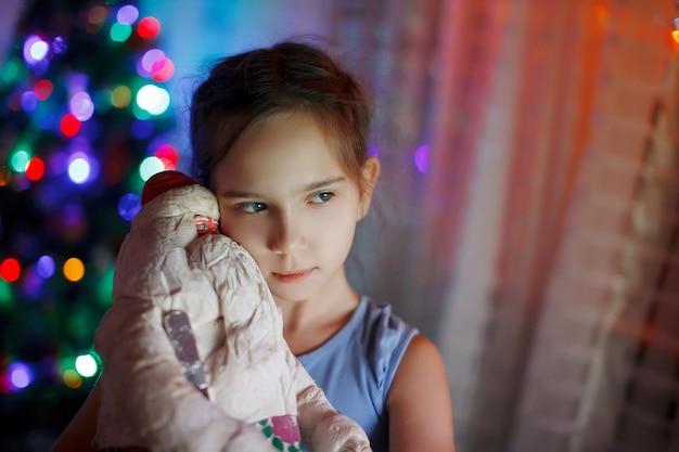 Bambina felice in attesa di un miracolo che abbraccia un babbo natale giocattolo