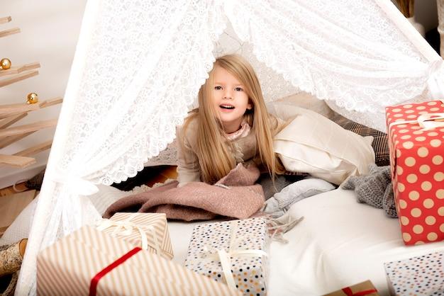Bambina felice tra cuscini e scatole regalo di natale