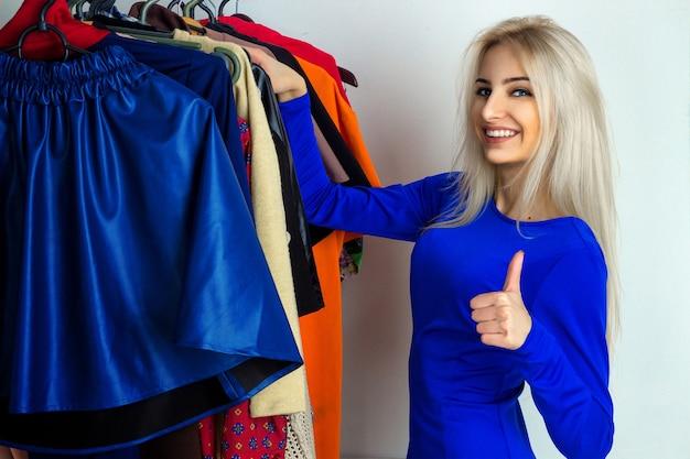 La ragazza felice sceglie i vestiti in negozio