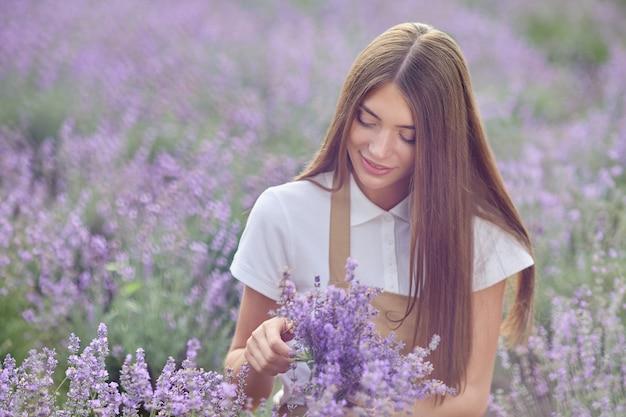 Ragazza felice che raccoglie fiori di lavanda in campo