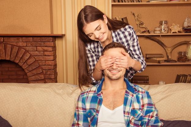 La ragazza felice ha sorpreso il suo ragazzo, coprendogli gli occhi con le mani