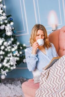 Ragazza felice che beve il tè del caffè a casa a natale