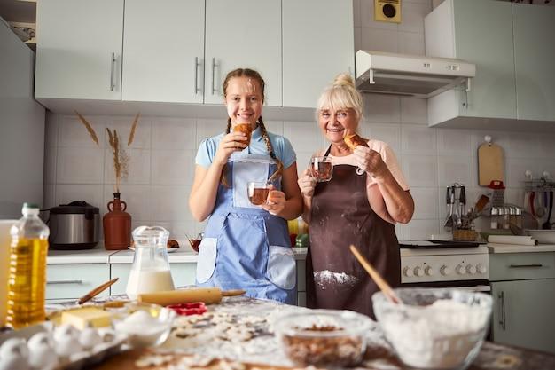 Ragazza felice che beve il tè con la sua amata nonna