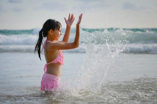 Una ragazza felice si diverte a giocare in mare a phuket, in thailandia.
