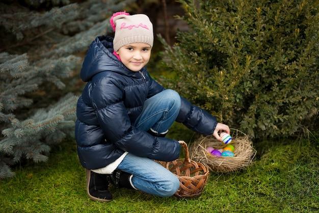 Ragazza felice che trova le uova di pasqua sul prato in cortile