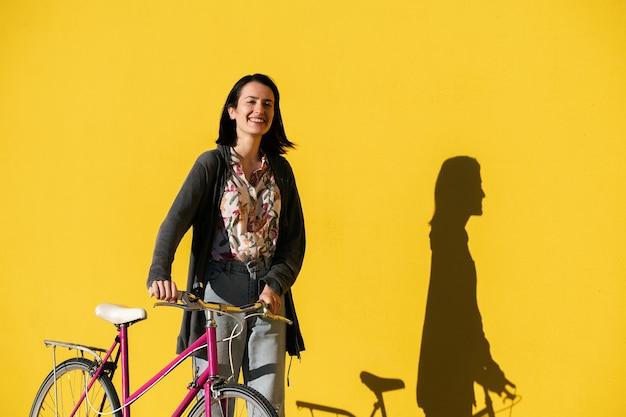 Ragazza felice davanti al muro giallo con una bici