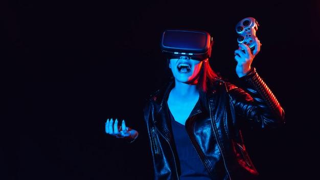 Giocatore felice della ragazza in vetri di realtà virtuale 3d con un joystick che gioca emozionalmente