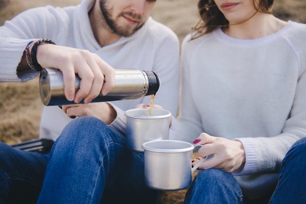 Felice ragazza e ragazzo con uno zaino turistico e una chitarra seduti in un campo e bere il tè da un thermos, concetto di storia d'amore di viaggio