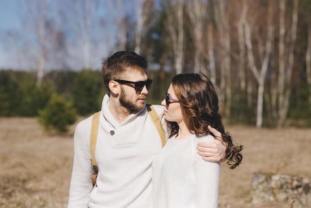 Felice ragazza e ragazzo con zaino turistico e chitarra che camminano nella natura, concetto di storia d'amore di viaggio, fuoco selettivo